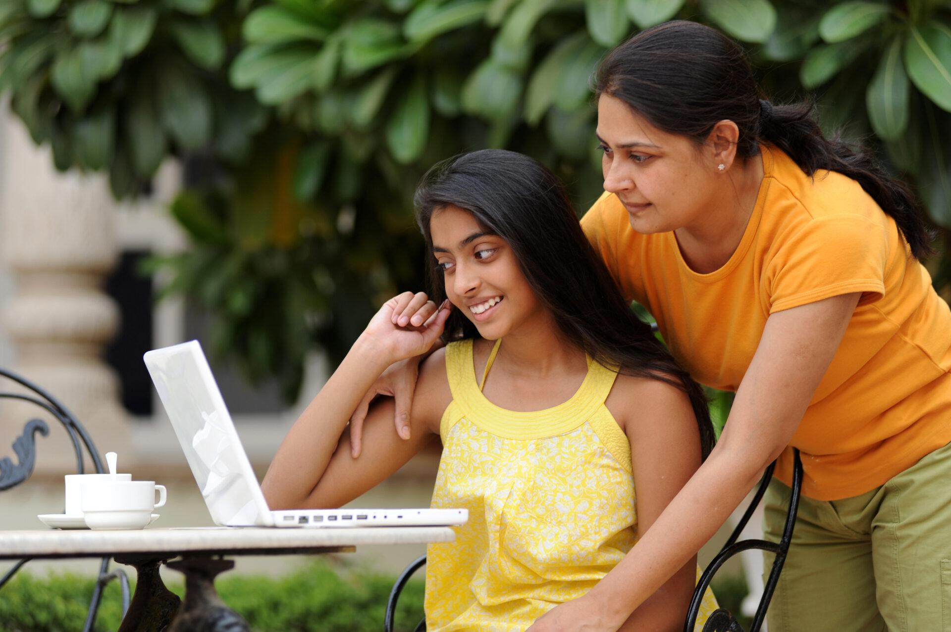 Loving mother and daughter using laptop together outdoors