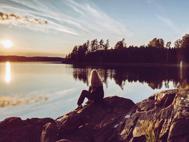 Suzanne sits on the banks of a lake in Norway. Her I can I will story is to get back here one day.