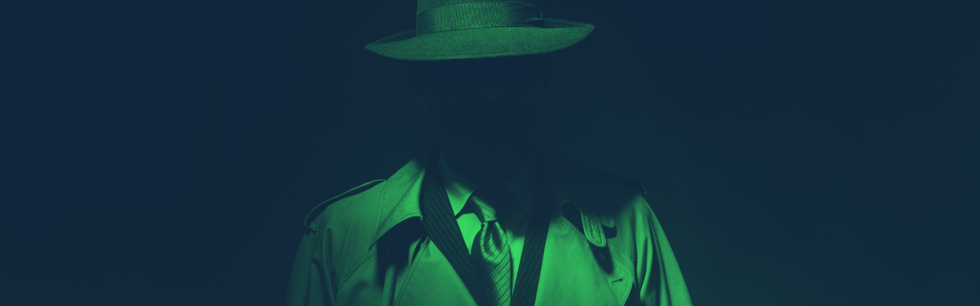 a mysterious person wearing a long coat and fedora hides in a shadow