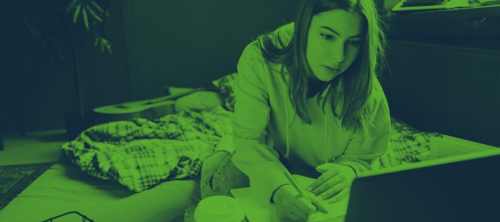 a young woman lying in bed studying on her laptop