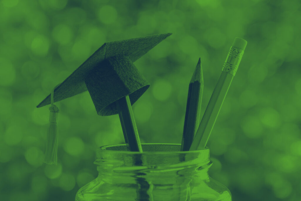 Pencils in a jar with a miniature mortarboard