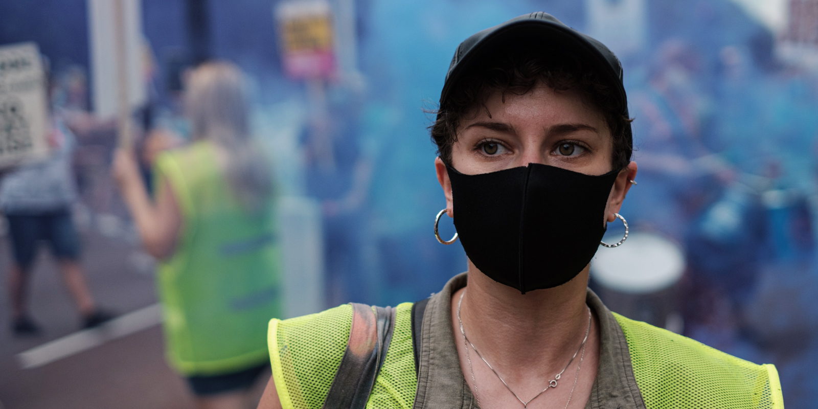 An image of a protest with a woman portrait covering her face with a mask