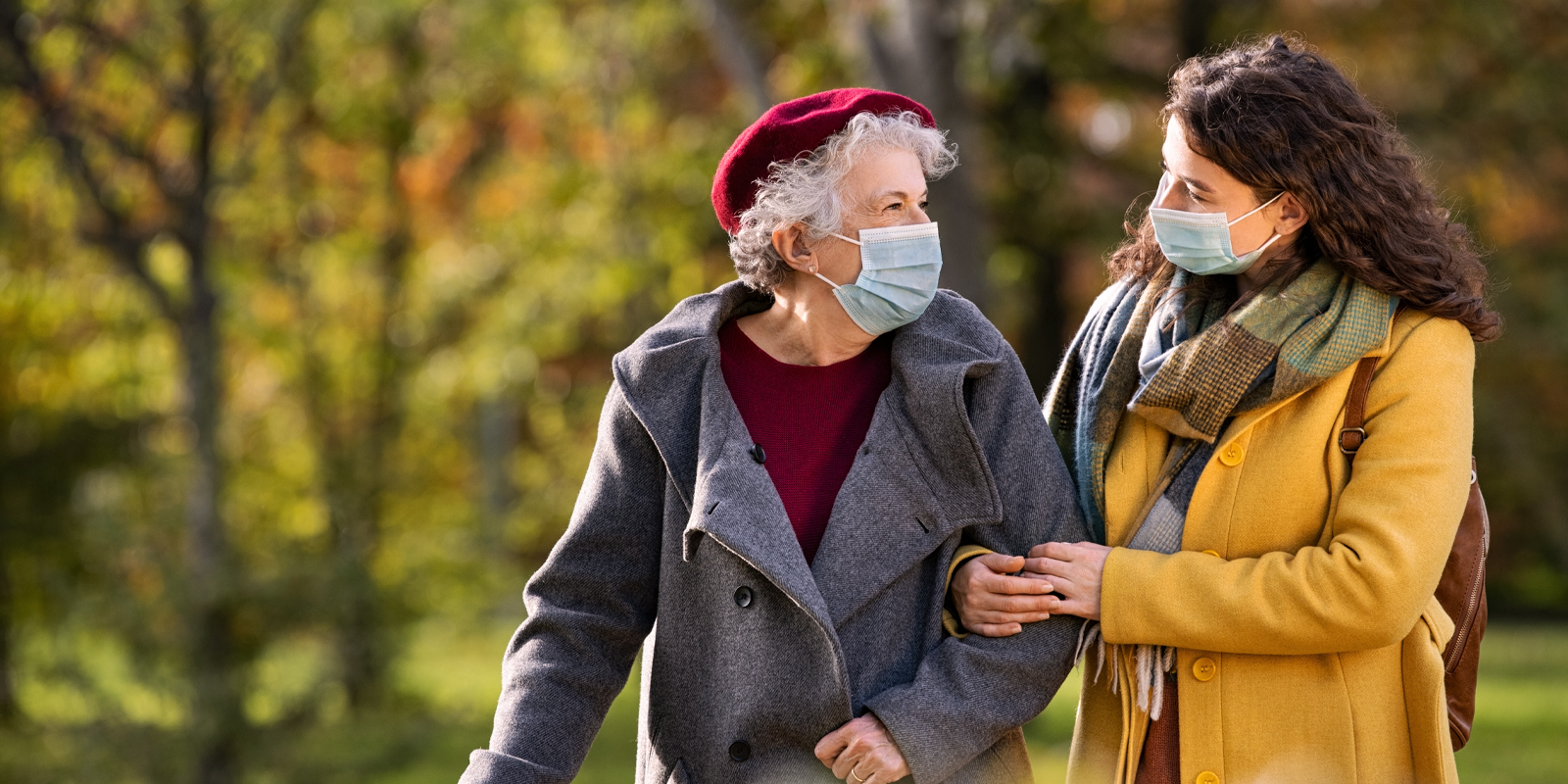 An image of a younger woman walking an older woman