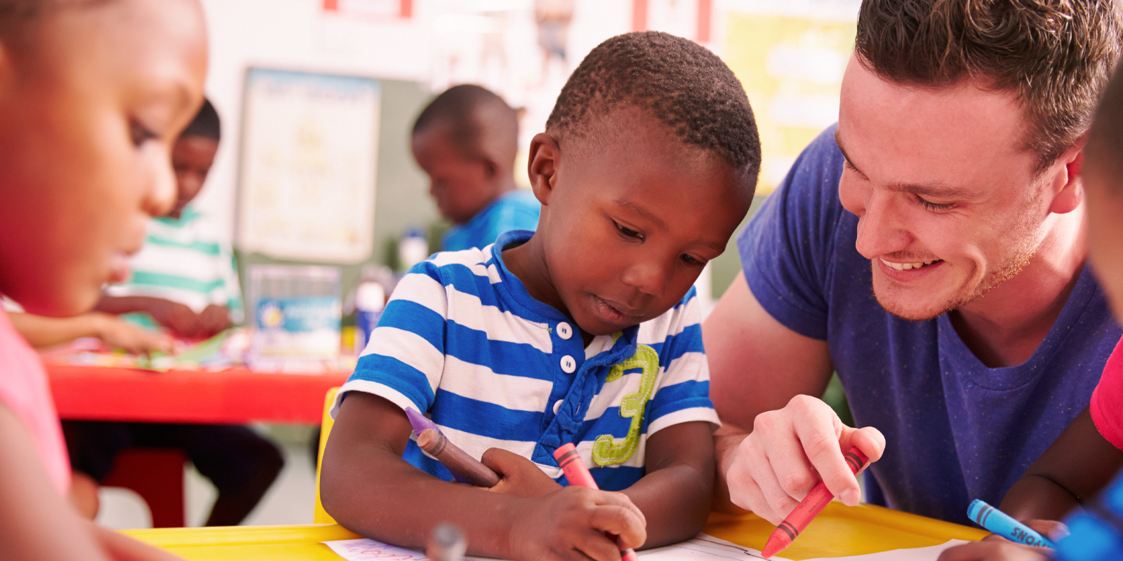 An image of small nursery kids colouring in crayons