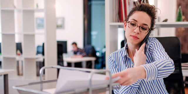 An image of a woman in an office, on the phone and handling paper work