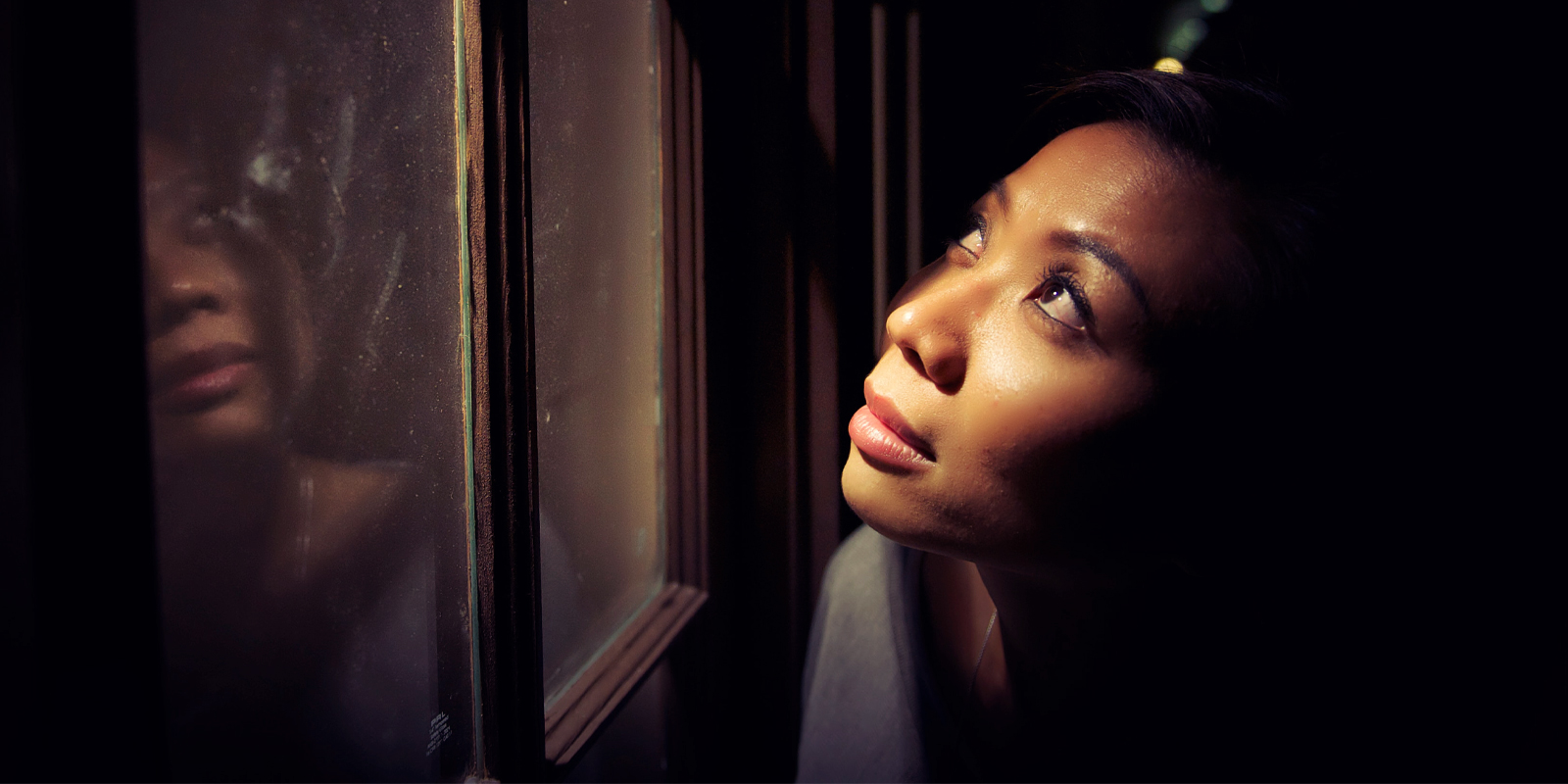 An image of a woman staring outside a window