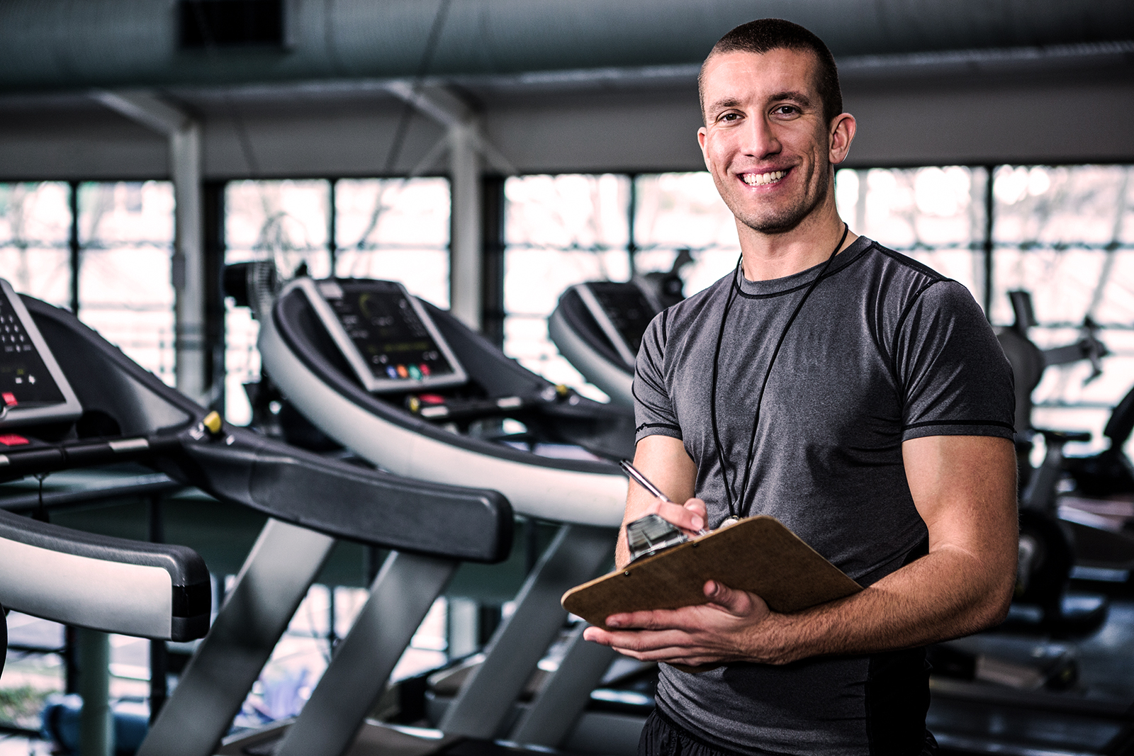Personal trainer holding clipboard smiling