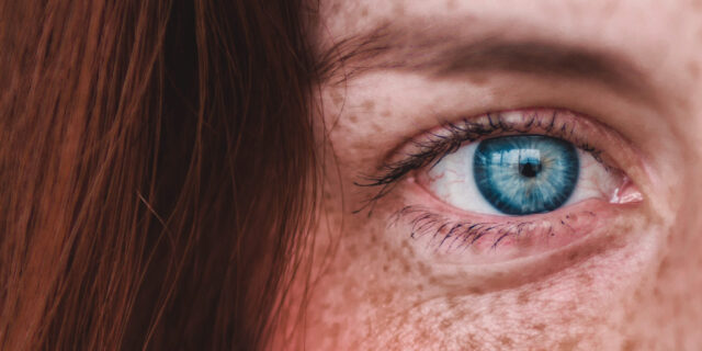 An image that is zoomed into a girls face, focusing on her blue eye
