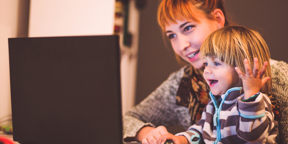 a young mother studies on her laptop in the company of her son