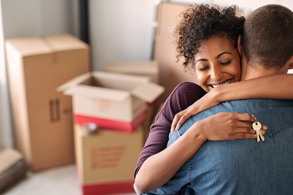 man and woman hugging in living room surrounded by boxes