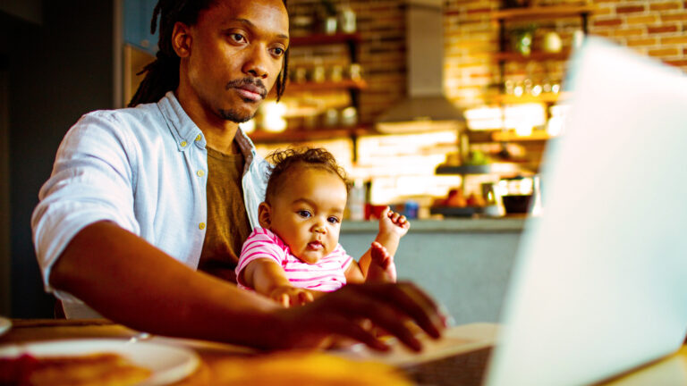 a young father sits at his laptop with his young child in his lap