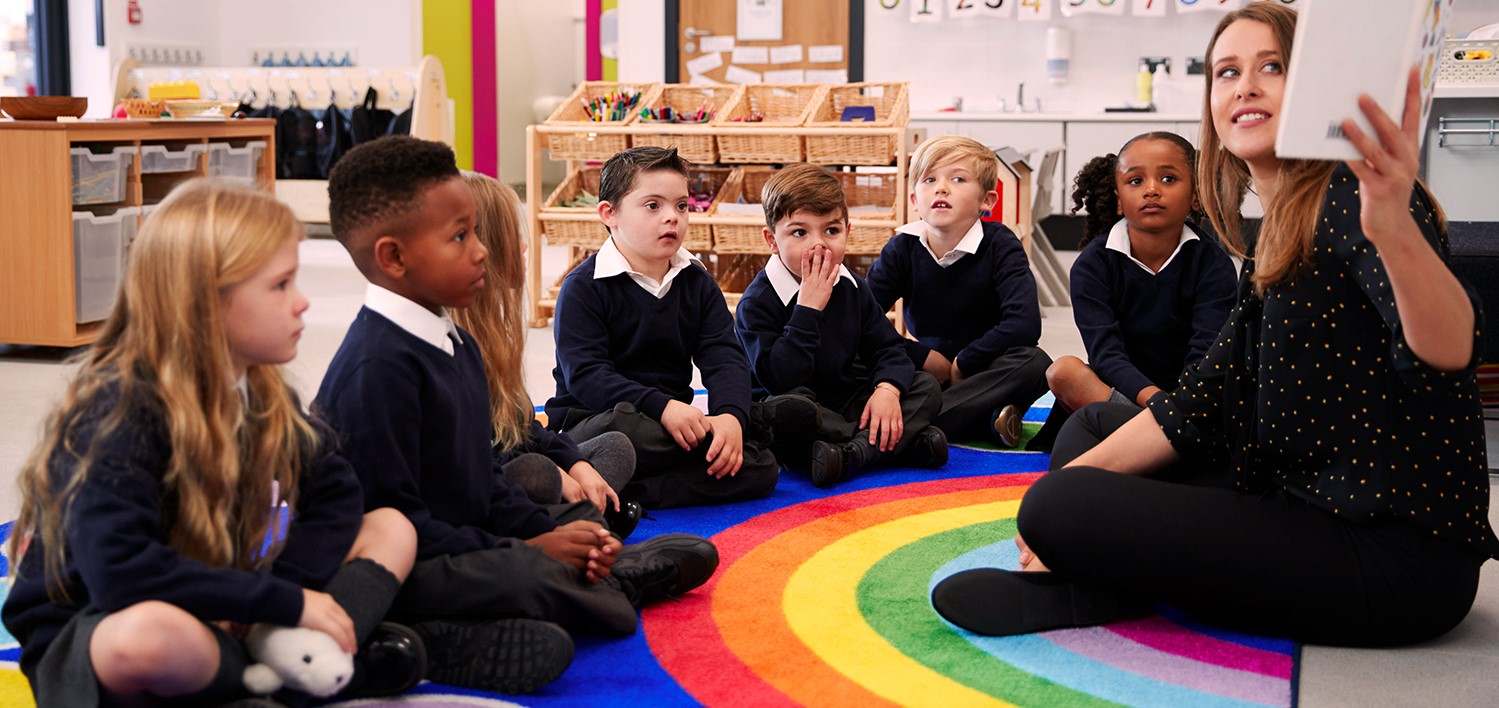Teaching Assistant sits with a group of children on a rainbow rug