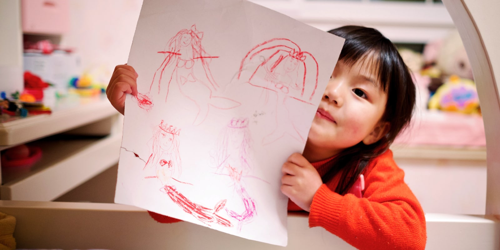 a young child shows off a drawing