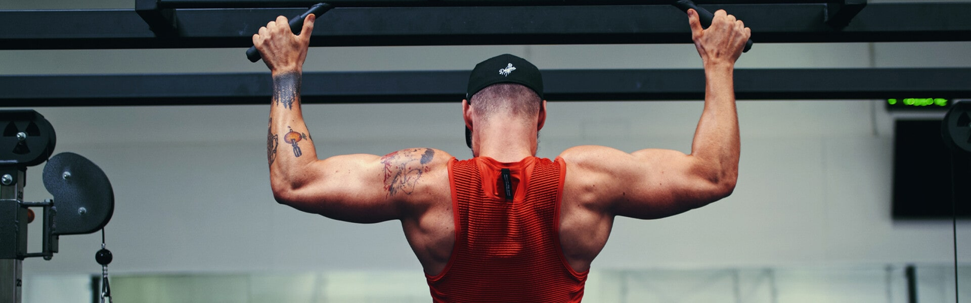 a tattooed man works out in a gym