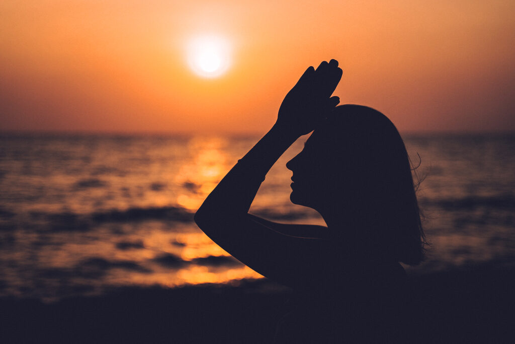 A woman meditating outside by the ocean with the sun reflecting on the water.